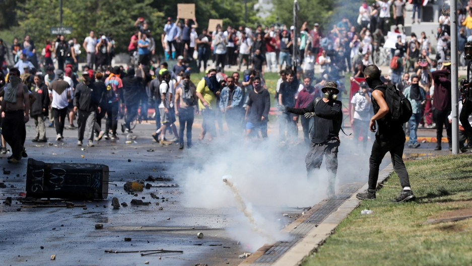 A crowd of demonstrators are shown amassed in the street with a tear gas canister bouncing in the middle of the frame.