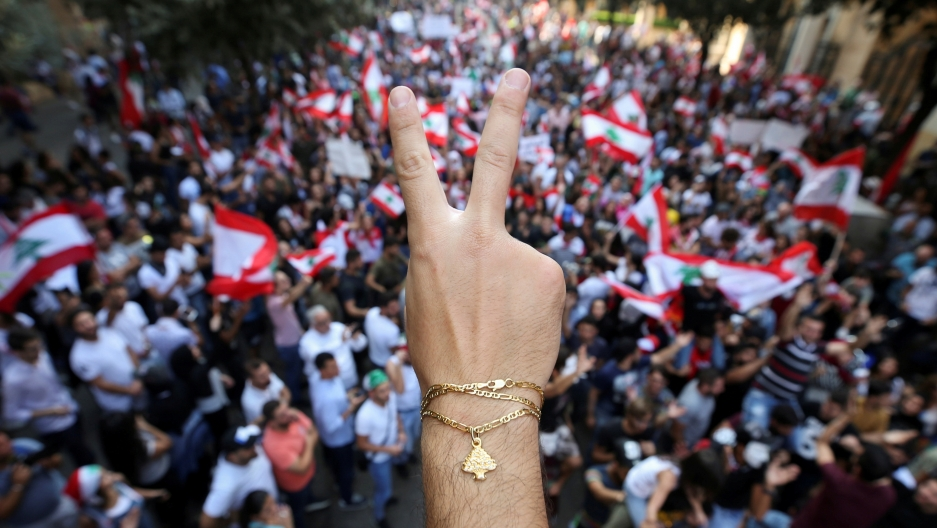 A demonstrator flashes a V sign during an anti-government protest in downtown Beirut, Lebanon October 21, 2019.