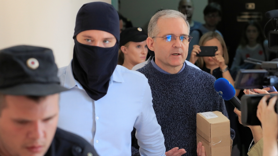 Three men walk into a court room, one is wearing a black mask, the other is holding a brown cardboard box.