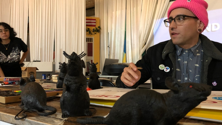 A person wearing a pink cap sits at a table near three large, black, plastic rats.