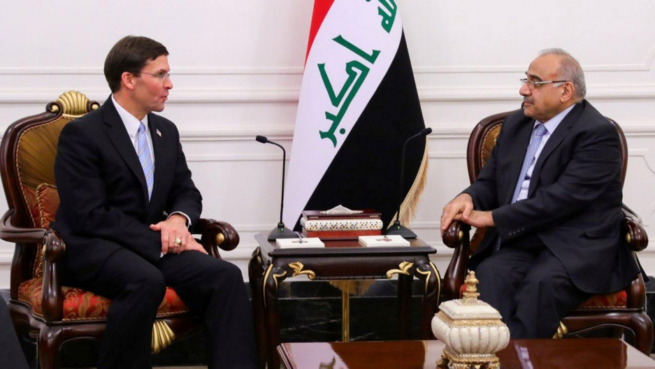 Iraqi Prime Minister Adel Abdul Mahdi is shown sitting across from US Defense Secretary Mark Esper with the Iraqi flag behind them.