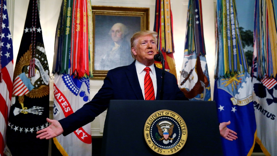 US President Donald Trump is shown standing at a podium with a seal for the US president with a painting of George Washington behind him.