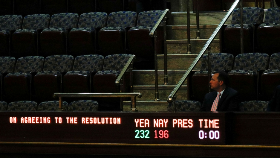 A man is shown sitting in the balcony of the US House with a vote tallying electric sign in front of him.