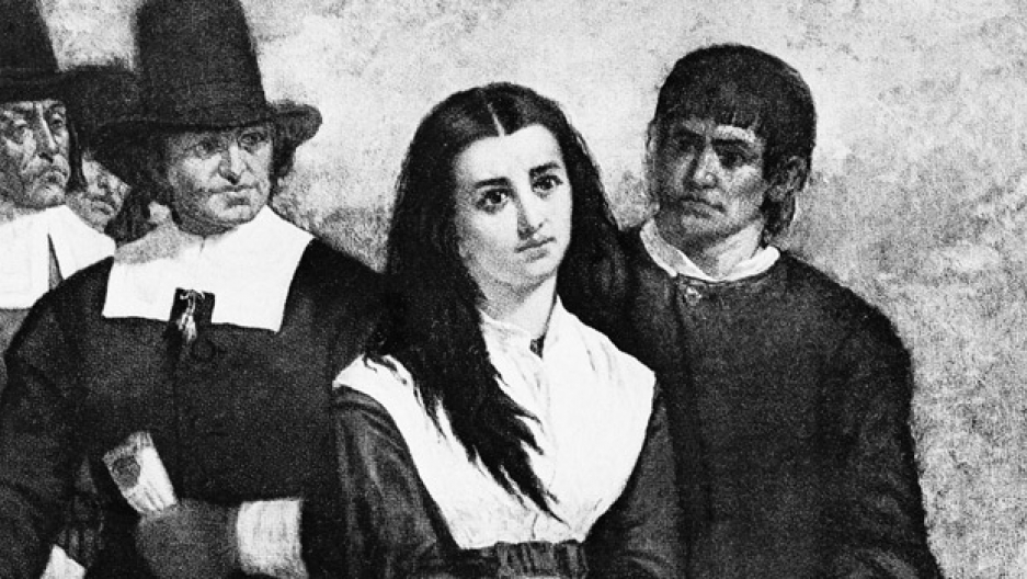 A black-and-white section of a painting of a woman surrounded by men in Puritan garb.