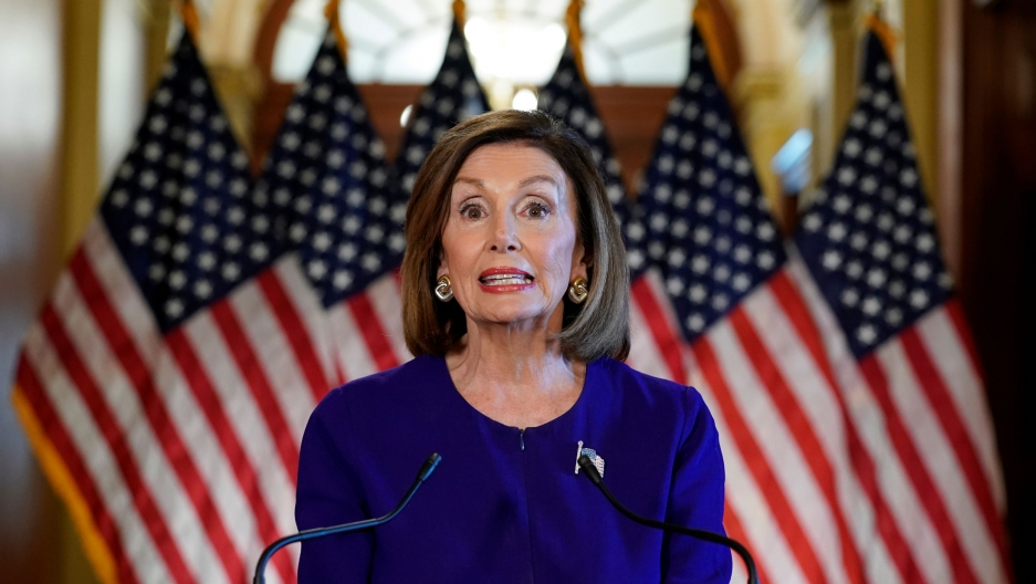 Nancy Pelosi in blue in front of American flags