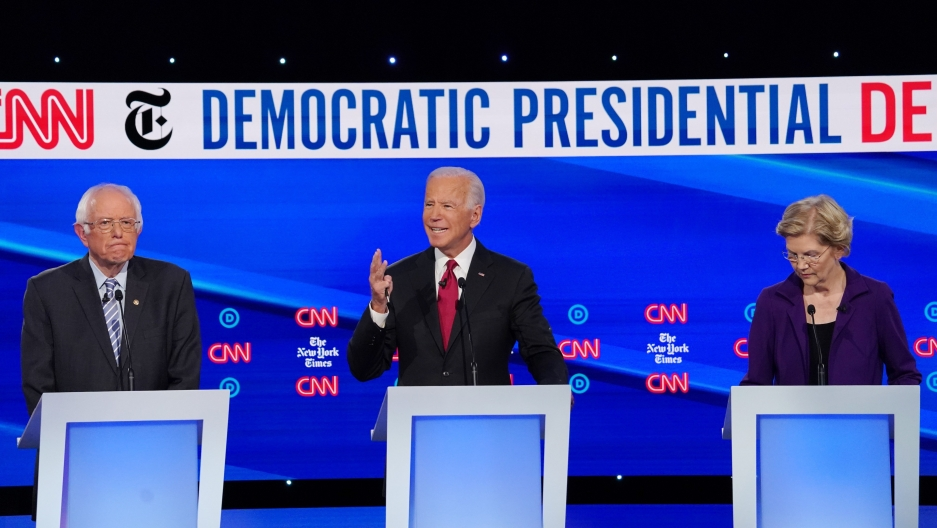 Bernie Sanders, Joe Biden and Elizabeth Warren stand behind podiums