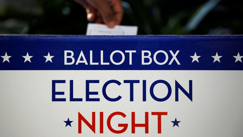 "A ballot box in red, white and blue says ""Election night ballot box"" on it"