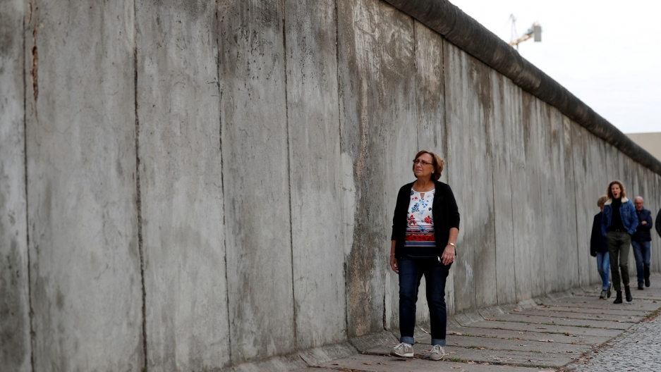 A woman walks along a tall concrete wall