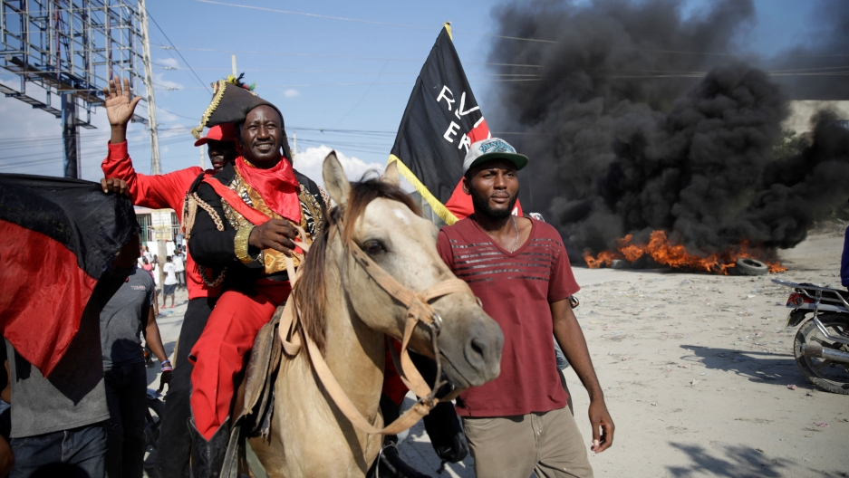A man on a horse wears a black and red colonial-era costume. Behind him is smoke from a fire.