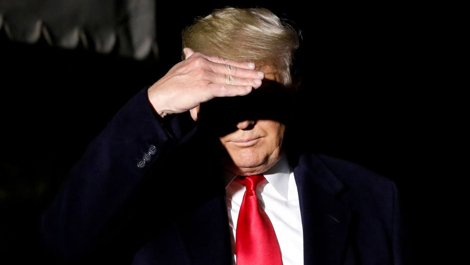 President Donald Trump is shown wearing a suit and red tie and using his hand to cover his eyes.