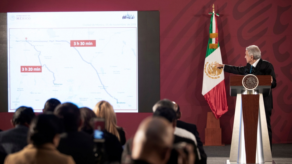 Mexico's President Andrés Manuel López Obrador is shown standing at a podium pointing toward a projection of a map with the Mexican flag behind him.