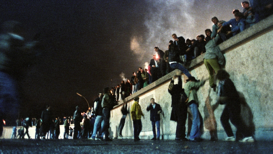 A large group of people are shown climbing on the Berlin Wall on the night it was opened.
