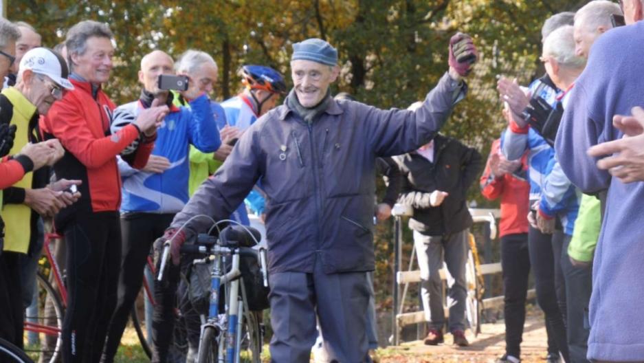 A man raises his hand while walking through a crowd.