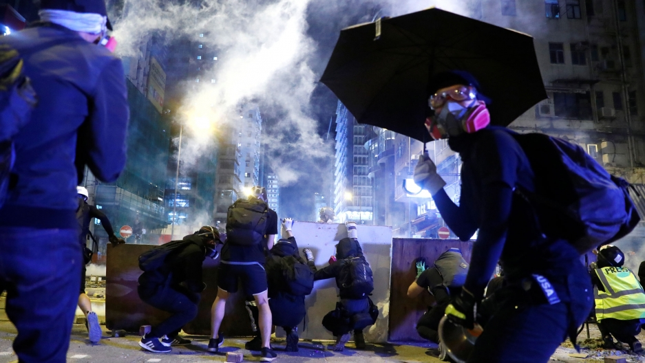 Several protesters are seen crouching behind boards and wearing all black with another protester wearing a gas mask and holding an umbrella.