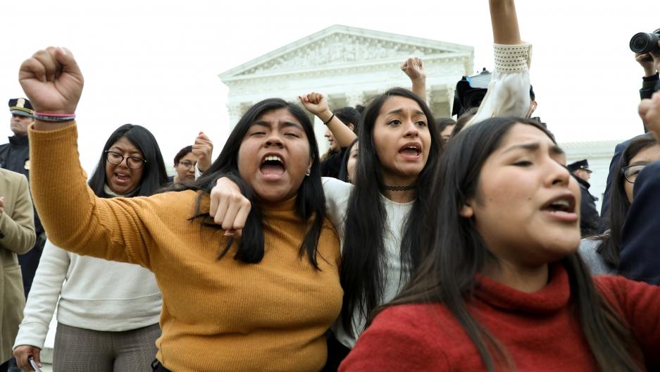 DACAplaintiffs walk arm-in-arm down from the US Supreme Court.