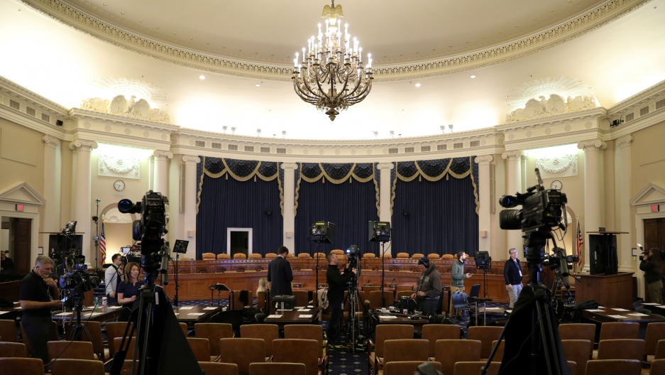 A House committee room is shown with a chandelier hanging from the ceiling and two television cameras placed among the seats.