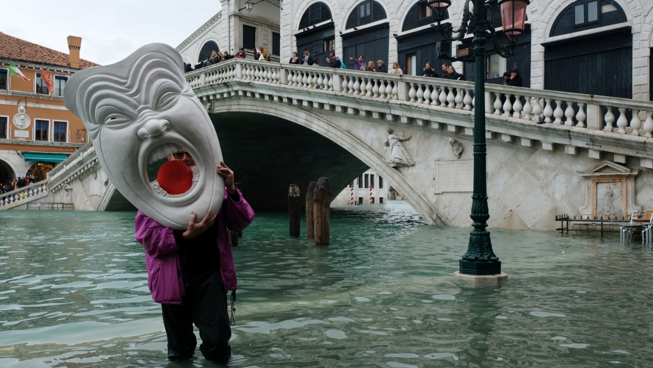 A man with a mask walks in a flooded street during a period of seasonal high water