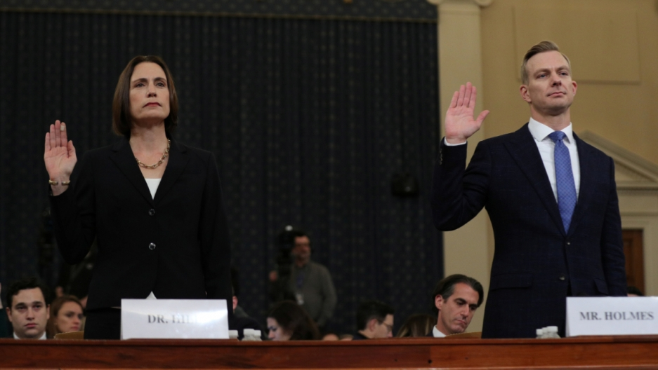 A man and a woman take the oath by raising their right hand.
