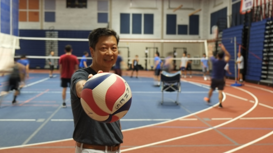 An Asian man holds a volleyball on the court