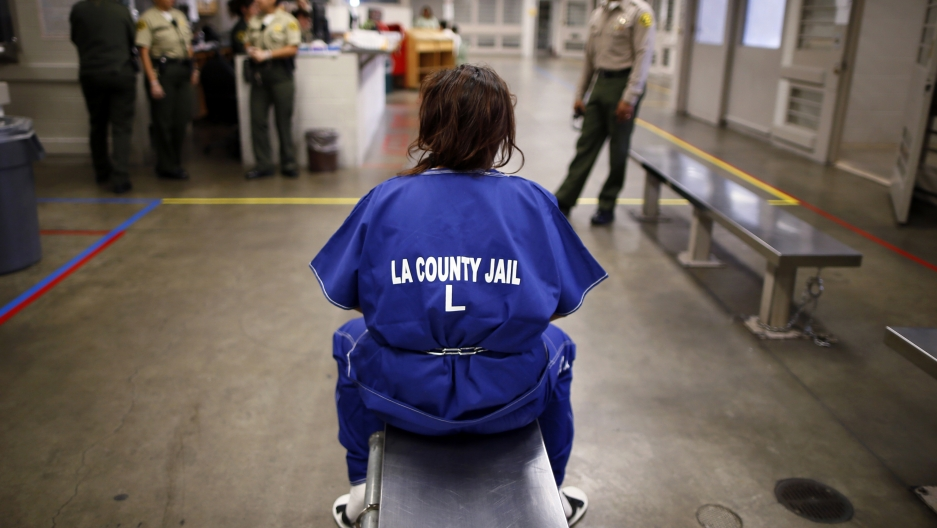 A woman sits on a bench in jail.