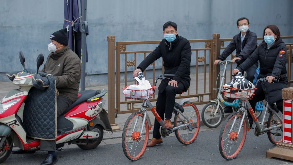 Three people are shown riding bicycles along with one riding a scooter and all wearing face masks.