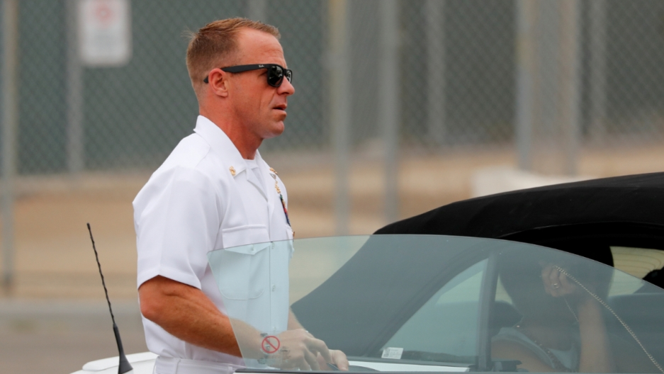 A man in a white navy uniform and black sunglasses walks into a car