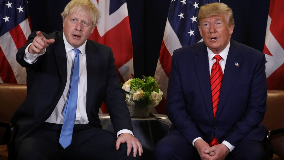 Donald Trump and Boris Johnson sit next to each other.