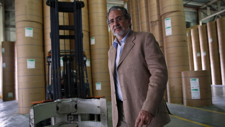 MiguelHenriqueOtero, editor and president of El Nacional, one of Venezuela's main national newspapers, walks past paper rolls at the newspaper's building in Caracas on April 11, 2014. Since 2015 he has lived in self-imposed exile in Madrid, Spain.