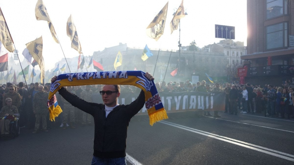"""A protester holdinga """"Ukraine"""" scarf poses during the """"march against capitulation"""" on Oct. 14, 2019, in Kyiv, Ukraine."""