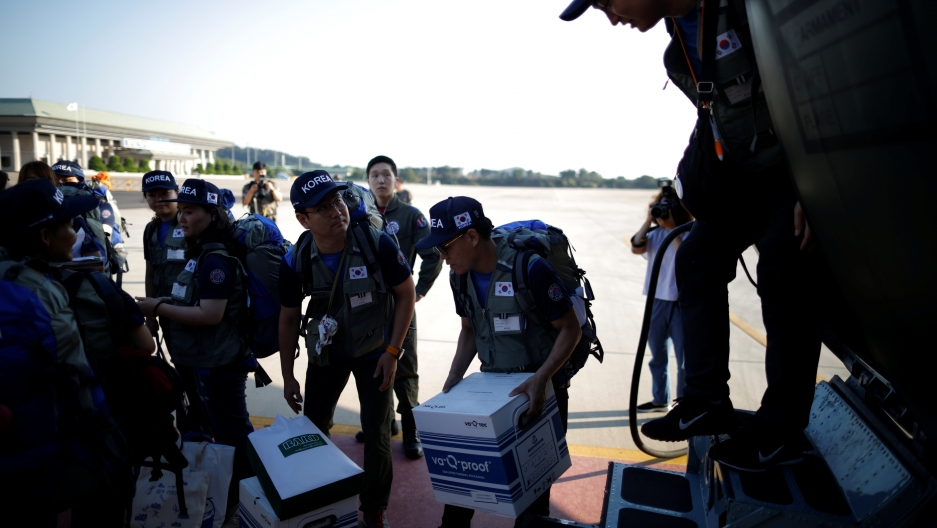 Military personnel carry disaster relief boxes.
