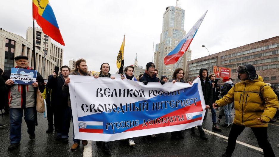 "People walk with a banner that reads: ""Great Russia, Free internet""."