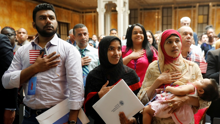 New citizens stand during the National Anthem at a USCitizenshipand Immigration Services (USCIS) naturalizationceremonyat the New York Public Library in Manhattan, New York, onJuly 3, 2018.