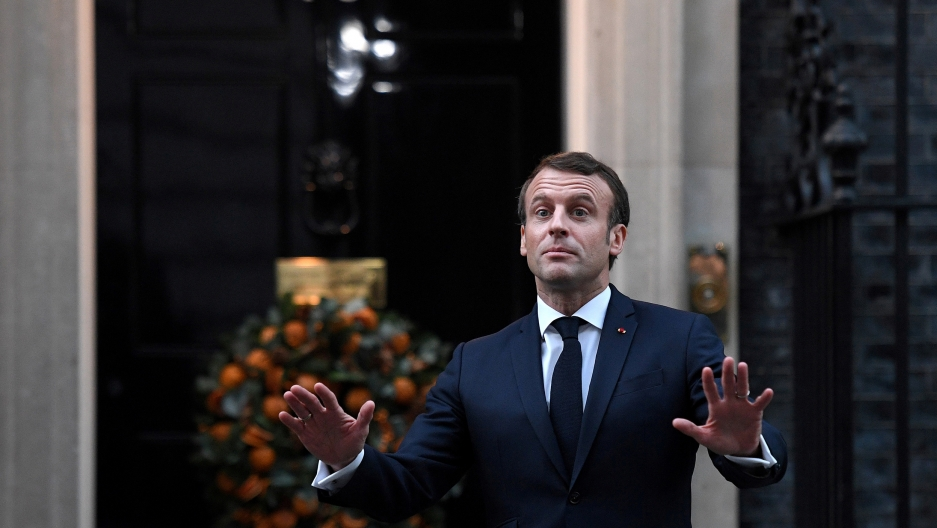 France's President Emmanuel Macron is shown with both of his hands outstretched and wearing a blue suit.