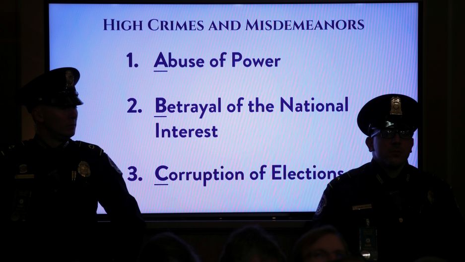 US Capitol police officers are shown in shadow standing in front of a brightly lit TV monitor displaying several sentences of text related to US President Donald Trump's alleged impeachable offenses.