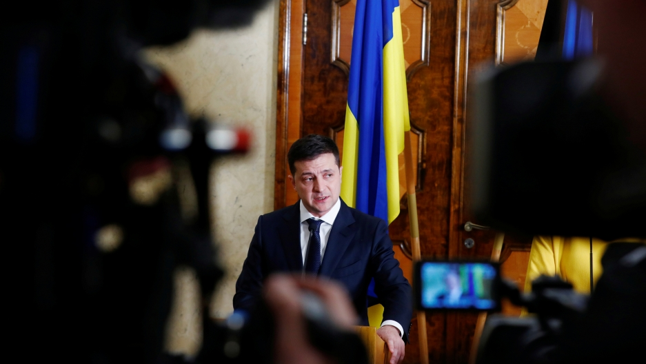 Ukraine's President Volodymyr Zelenskiy is shown standing at a podium with microphones and several cameras in the nearground.