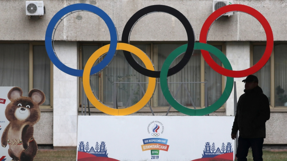 A man is shown in shadow in front of large sculpture of the Olympic rings.