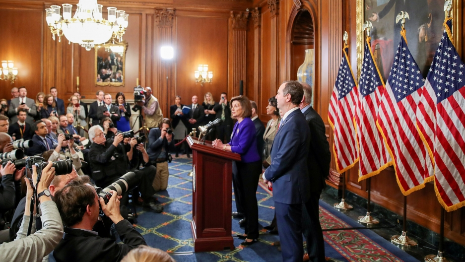 House Speaker Nancy Pelosi is shown standing at a wooden podium with microphones and several lawmakers standing behind her.