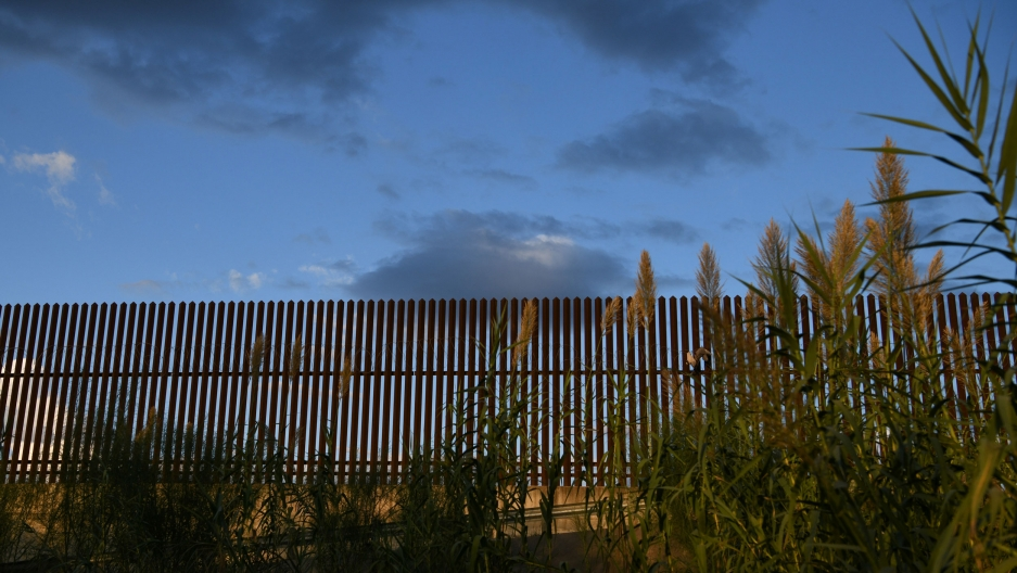 A section of a slatted border fence is shown with greenery in the nearground and dark clouds in the distance.