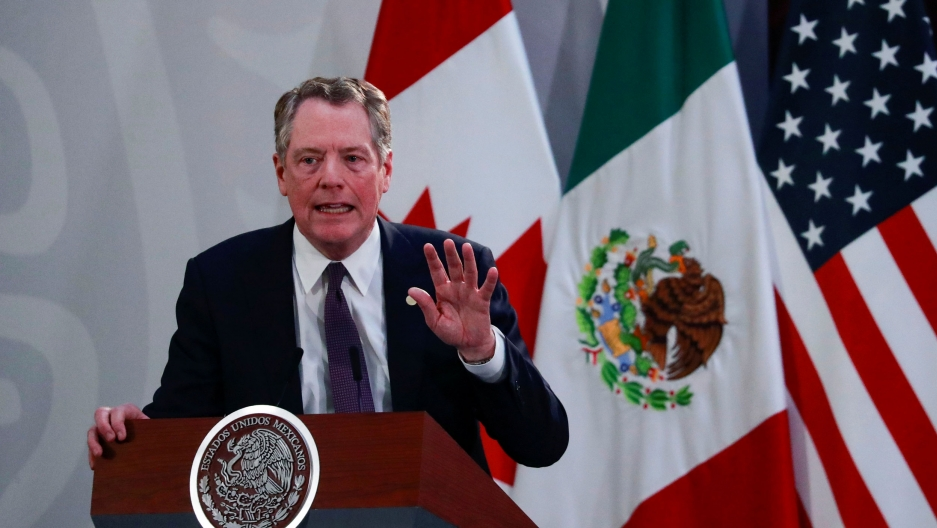US Trade Representative Robert Lighthizer is shown speaking from a podium with the US, Mexico and Canadian flags behind him.