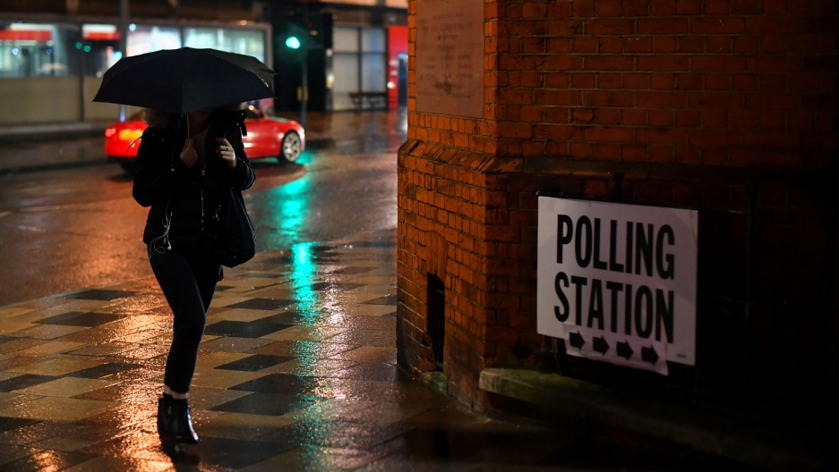 A woman is shown in shadow and carrying an umbrella walking next to a brick building with a polling station sign taped to the wall.