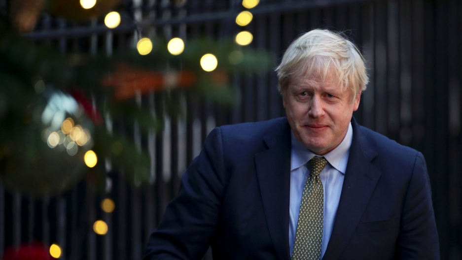 Britain's Prime Minister Boris Johnson is shown wearing a blue suit jacket and walking next to a slotted fence.