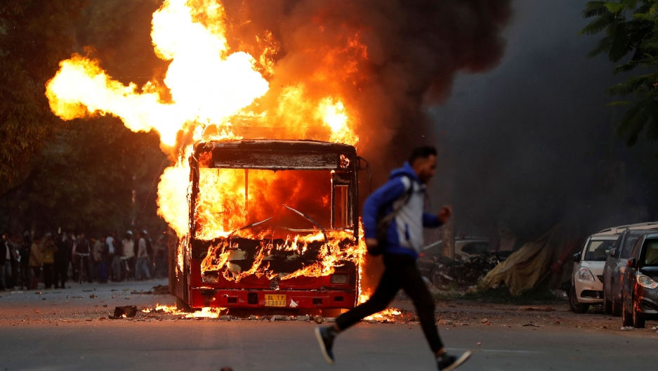 A man is shown in a blur running past the front of a bus on fire with large explosive-looking flames.