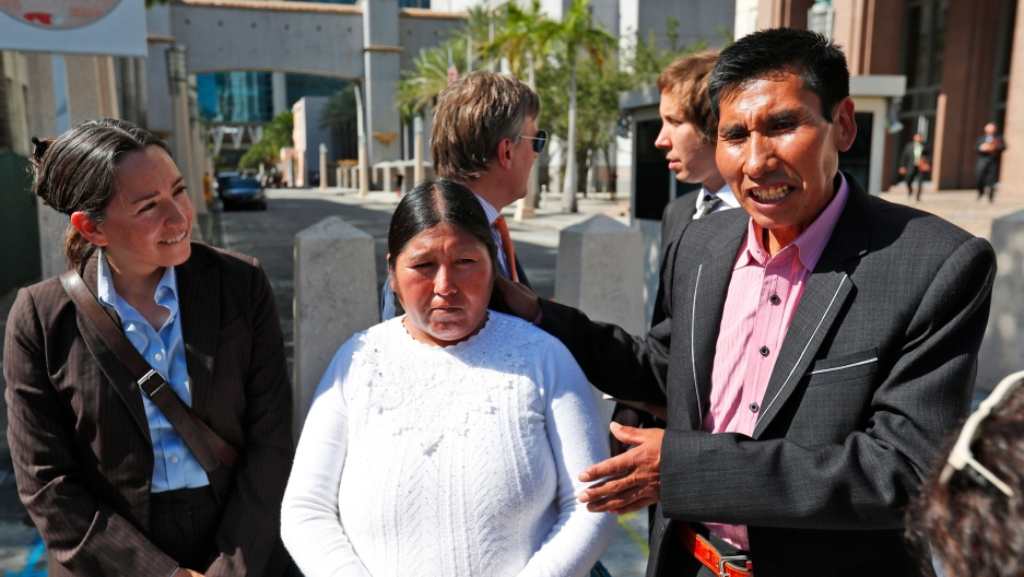 Eloy Rojas Mamani, right, gestures toward his wife Etelvina Ramos Mamani are shown standing next to each other with Eloy wearing a dark suit and Etelvina wearing a white top.