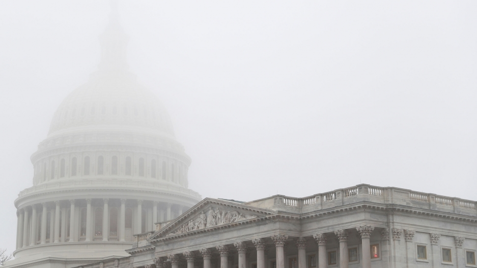 Heavy fog sits over the top of the US Capitol dome making it barely visible.