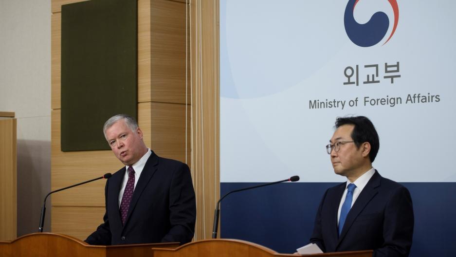 American man wearing dark blue suit speaks at podium standing next to Korean man wearing dark blue suit.