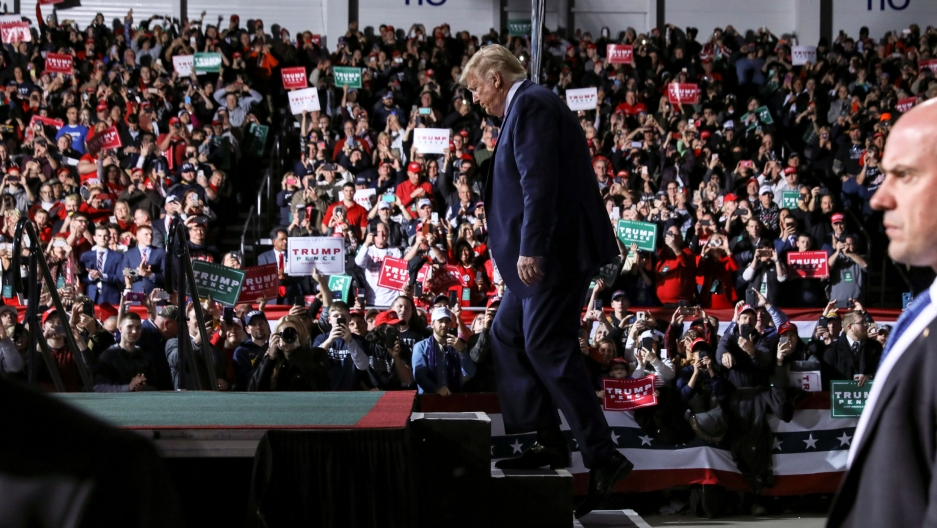 US President Donald Trump is shown walking up the steps of a stage with an audience in the distance.