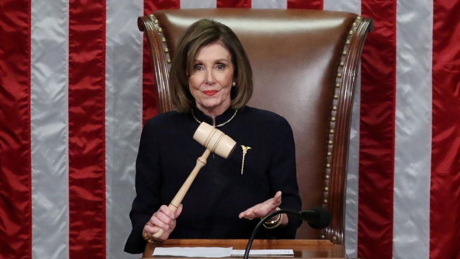US Speaker of the House Nancy Pelosi wields the gavel and stands in front of a large US flag.