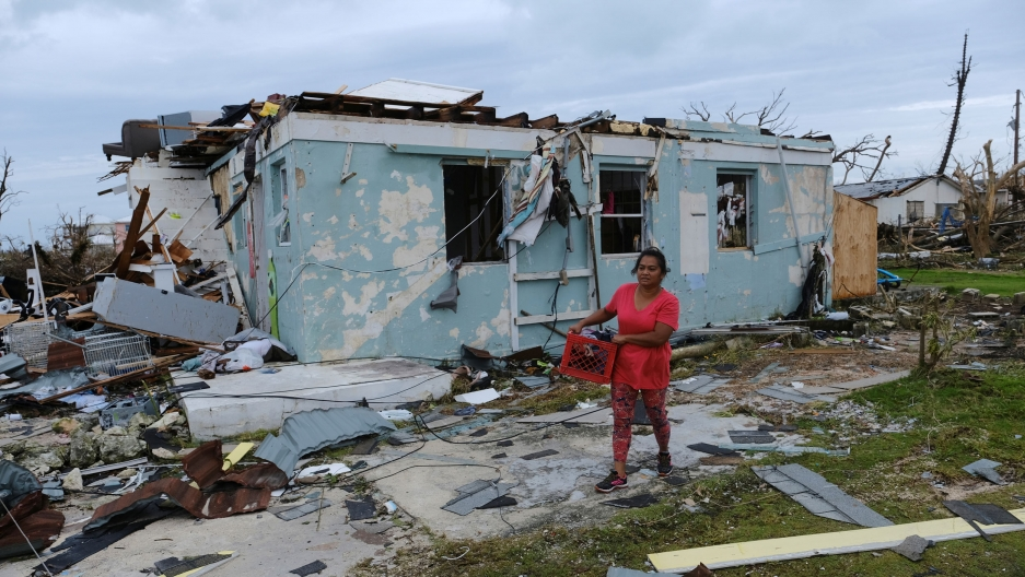 A woman is shown wearing a red shirt and walking with a crate next to a heavily damaged home.