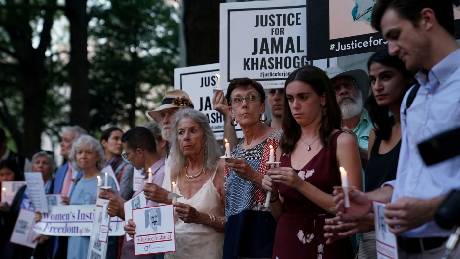 "A large group of people are shown, many with burning candles, and others holding signs that that read, ""Justice of Jamal Khashoggi."""
