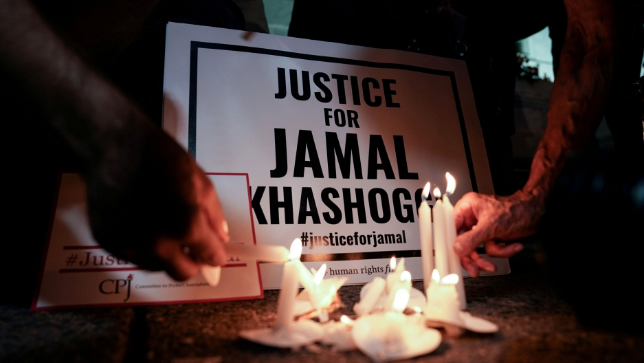 "Several white candles are burning in front of a sign that reads, ""Justice for Jamal Khashoggi."""